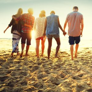 Group of people standing on beach, some discussing IVF | Fertility Specialists Medical Group | San Diego, CA