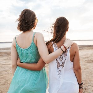 Two girls walking on the beach talking about endometriosis and infertility | Fertility Specialists Medical Group | San Diego, CA