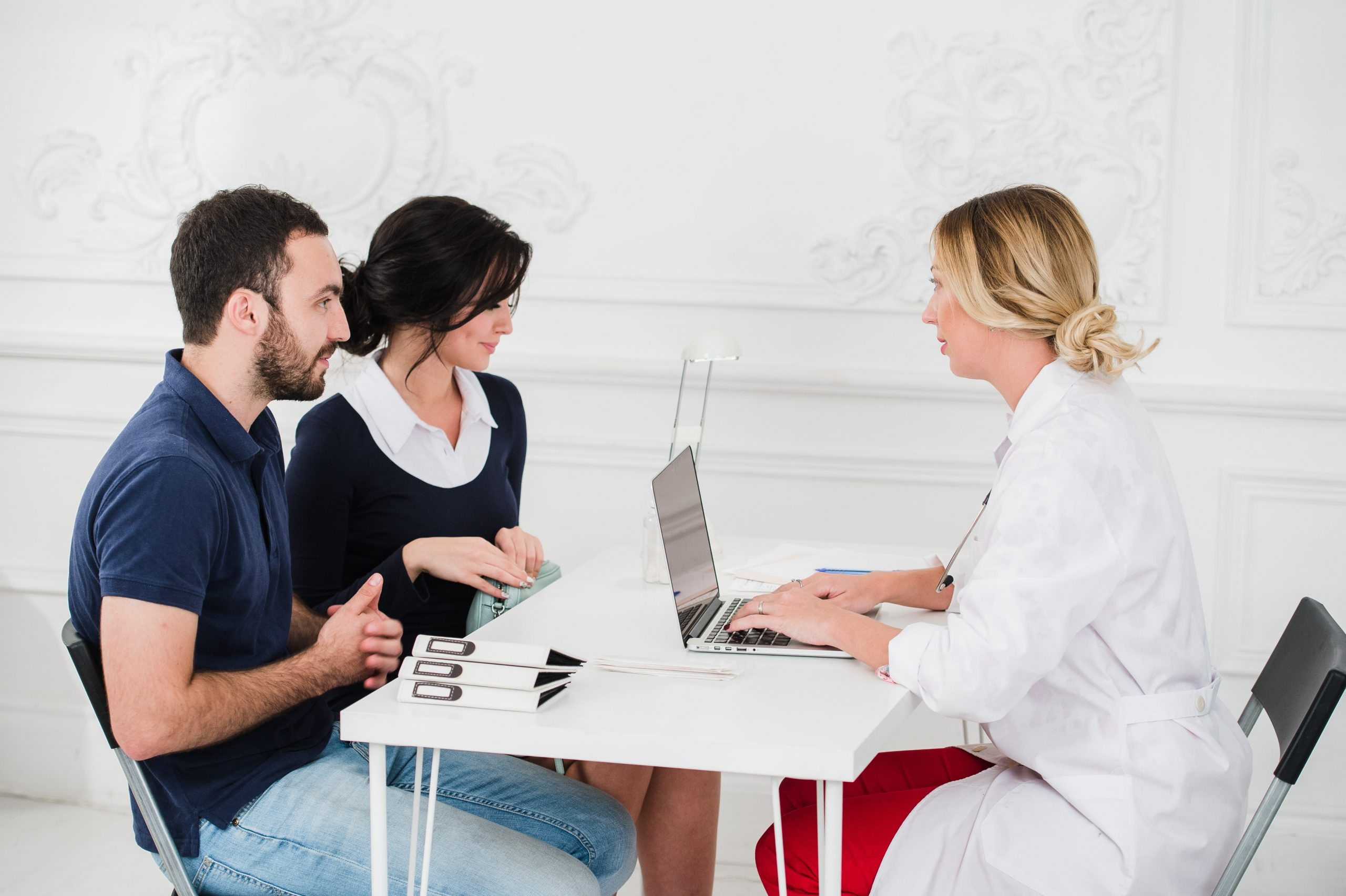 Young couple meeting with IVF doctor to learn about PGT (preimplantation genetic testing)