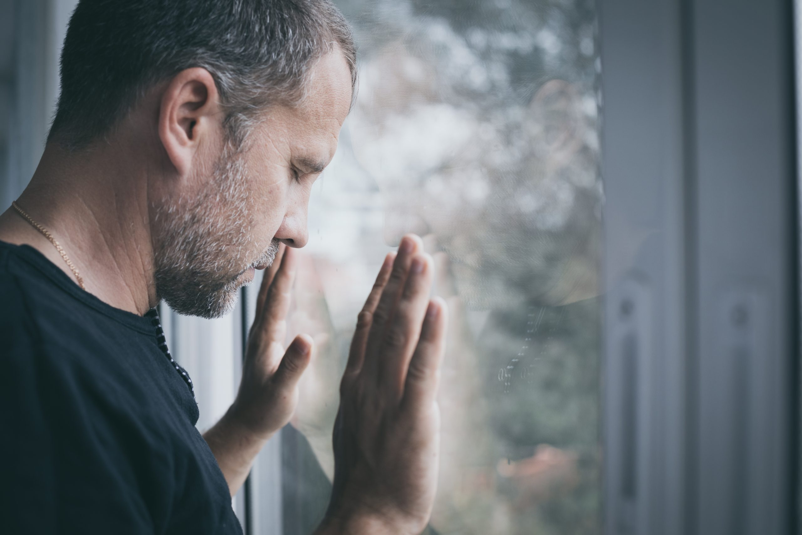 Man wih hands on window thinking about his fertility issues.