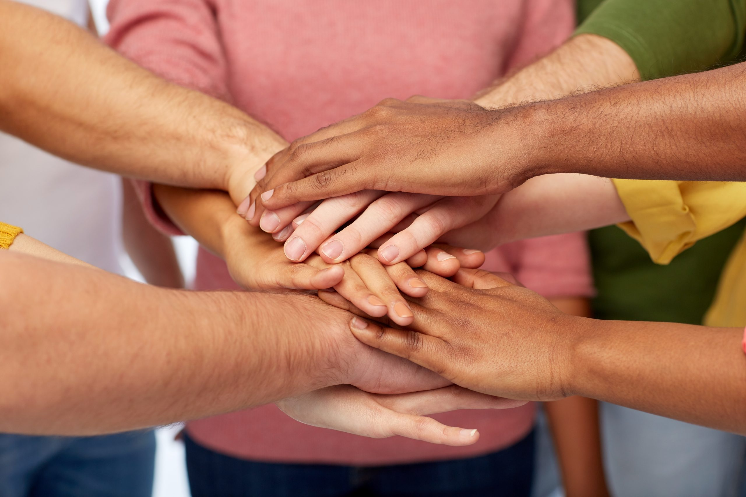 Team placing hands on top of one another's hands. Teamwork is what makes FSMG special