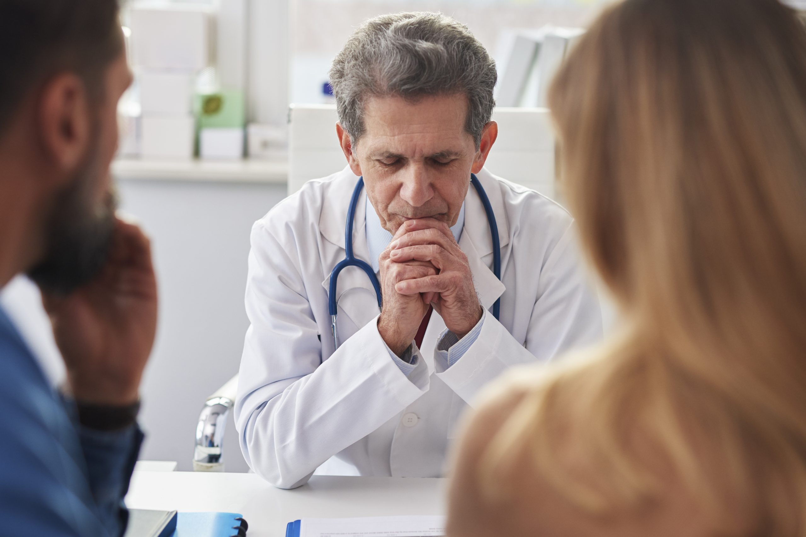 Fertility doctor with young couple discussing relationship between endometriosis, infertility, miscarriages, and stroke.