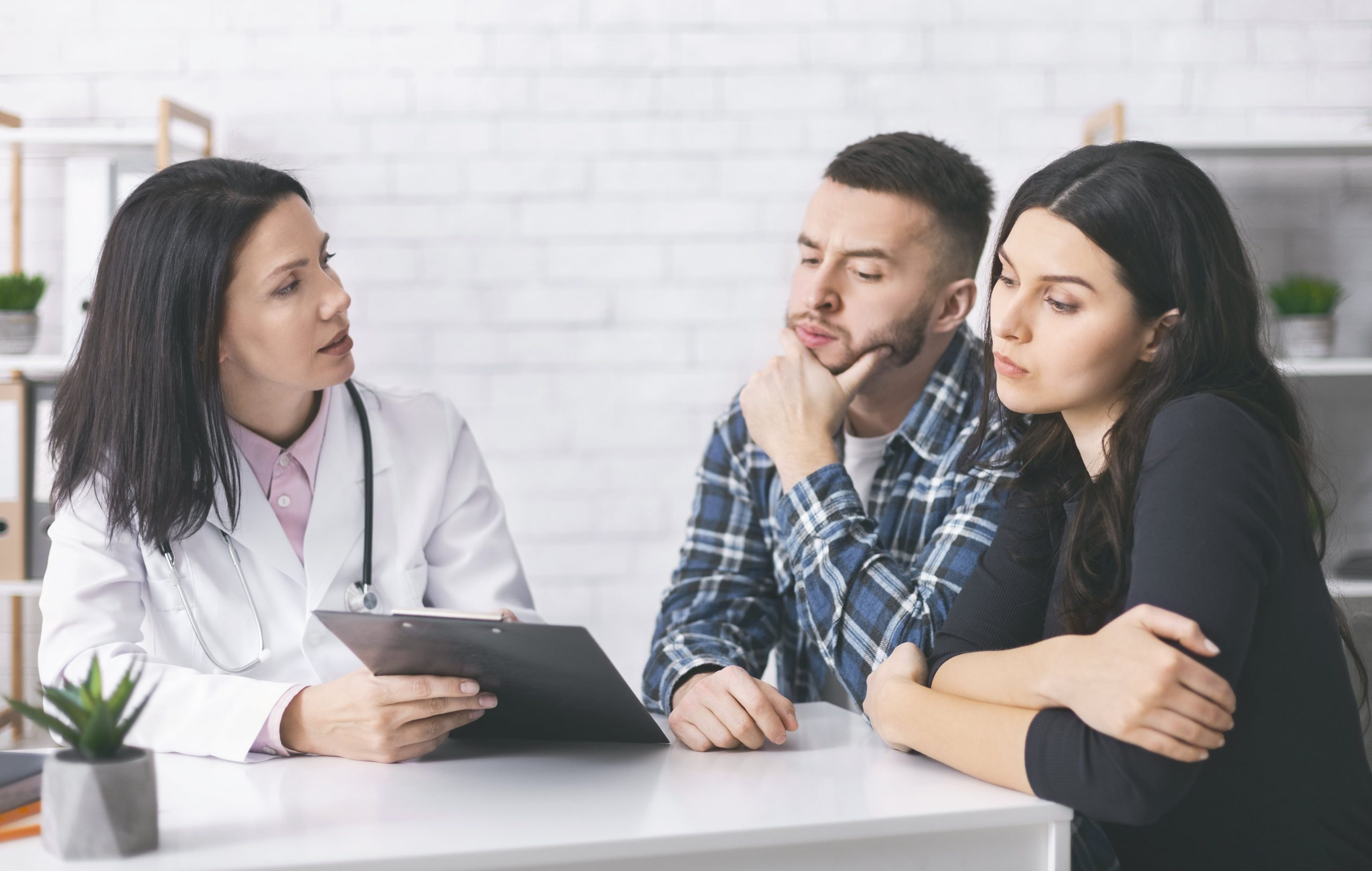 Young man and woman sitting at desk with fertility doctor discussing PCOS.