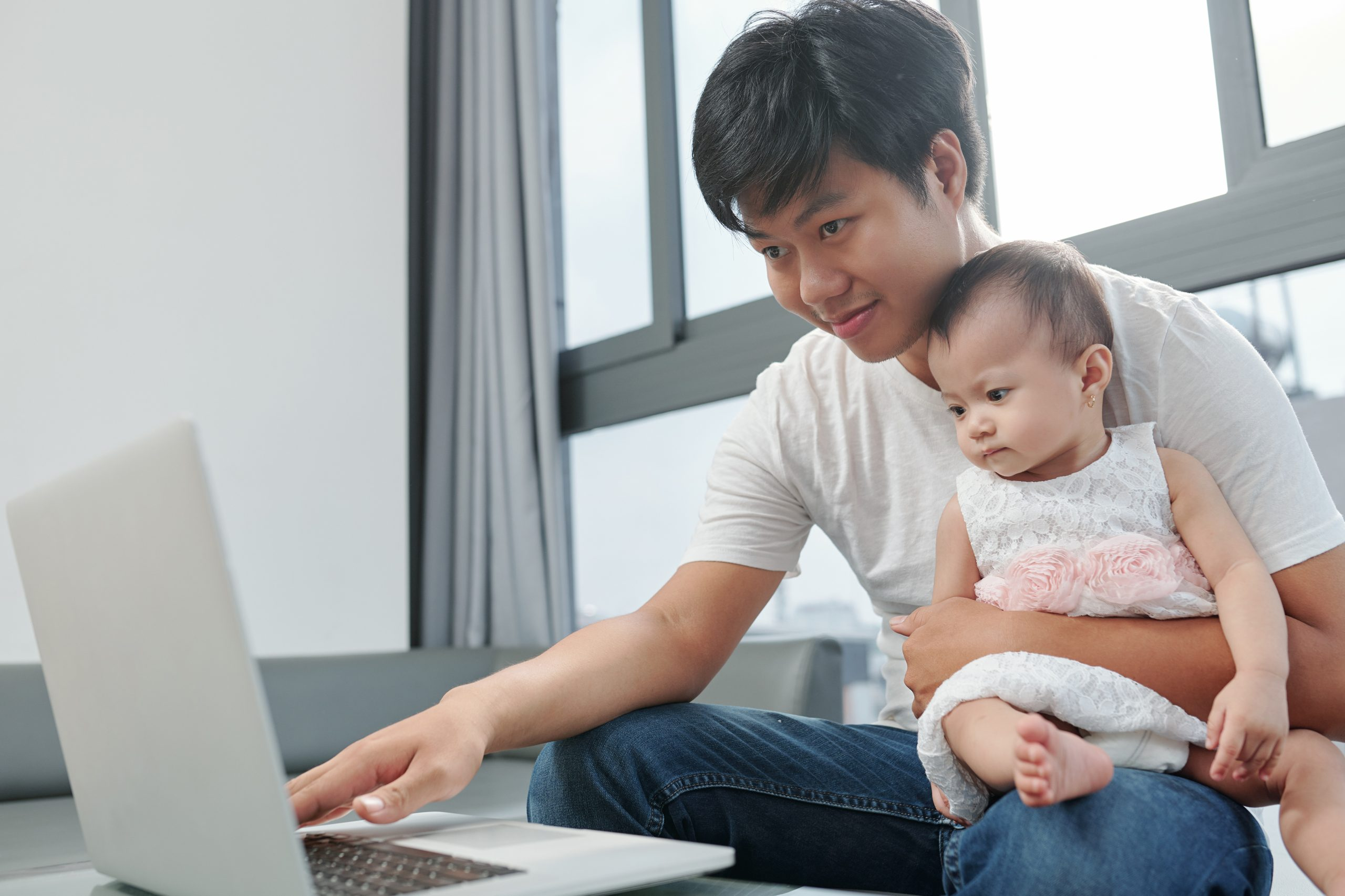 Smiling young Vietnamese man working on laptop at home and testing new computer program with little dauhgter sitting on his laps