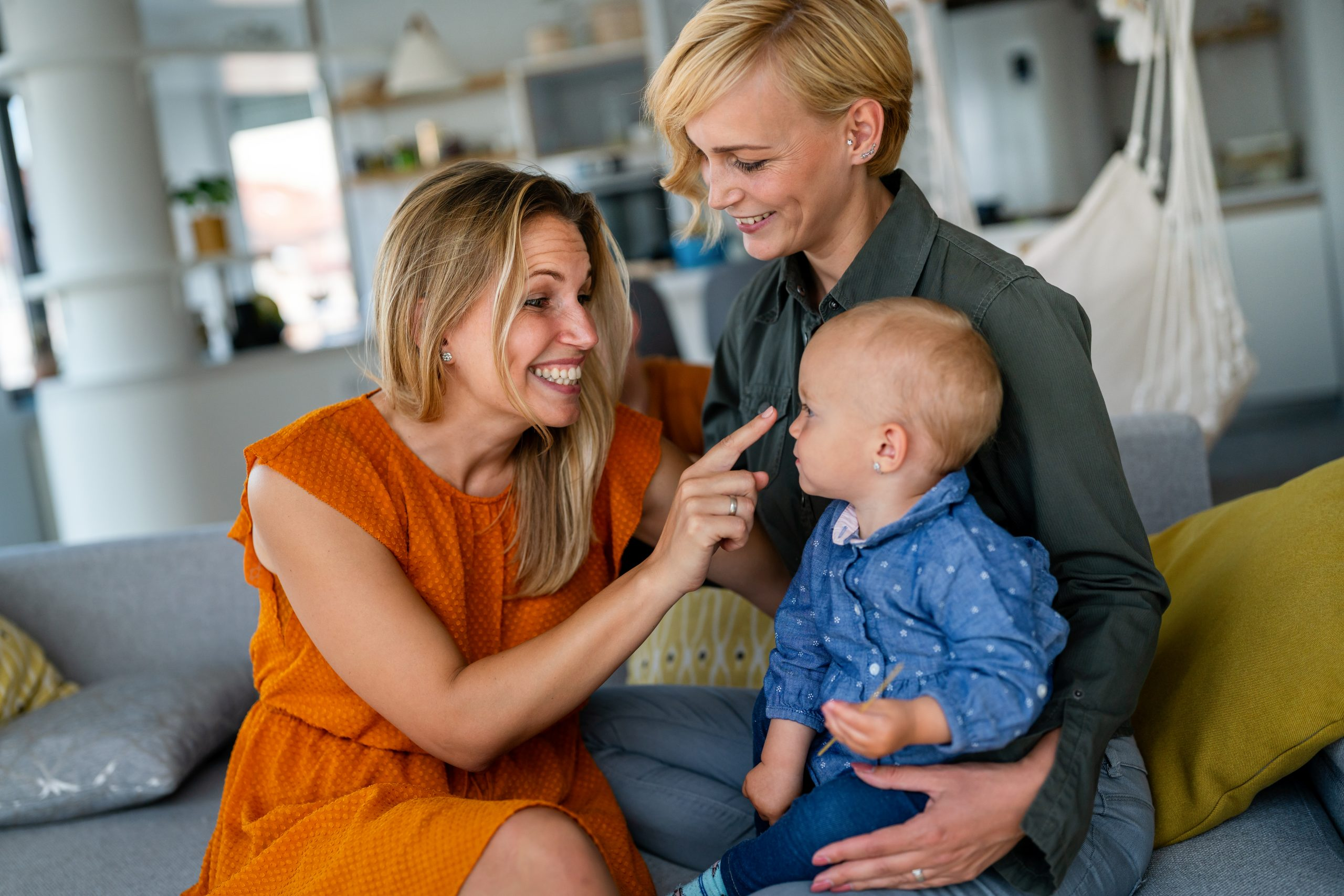 Happy lesbian couple with little girl at home after IVF family building